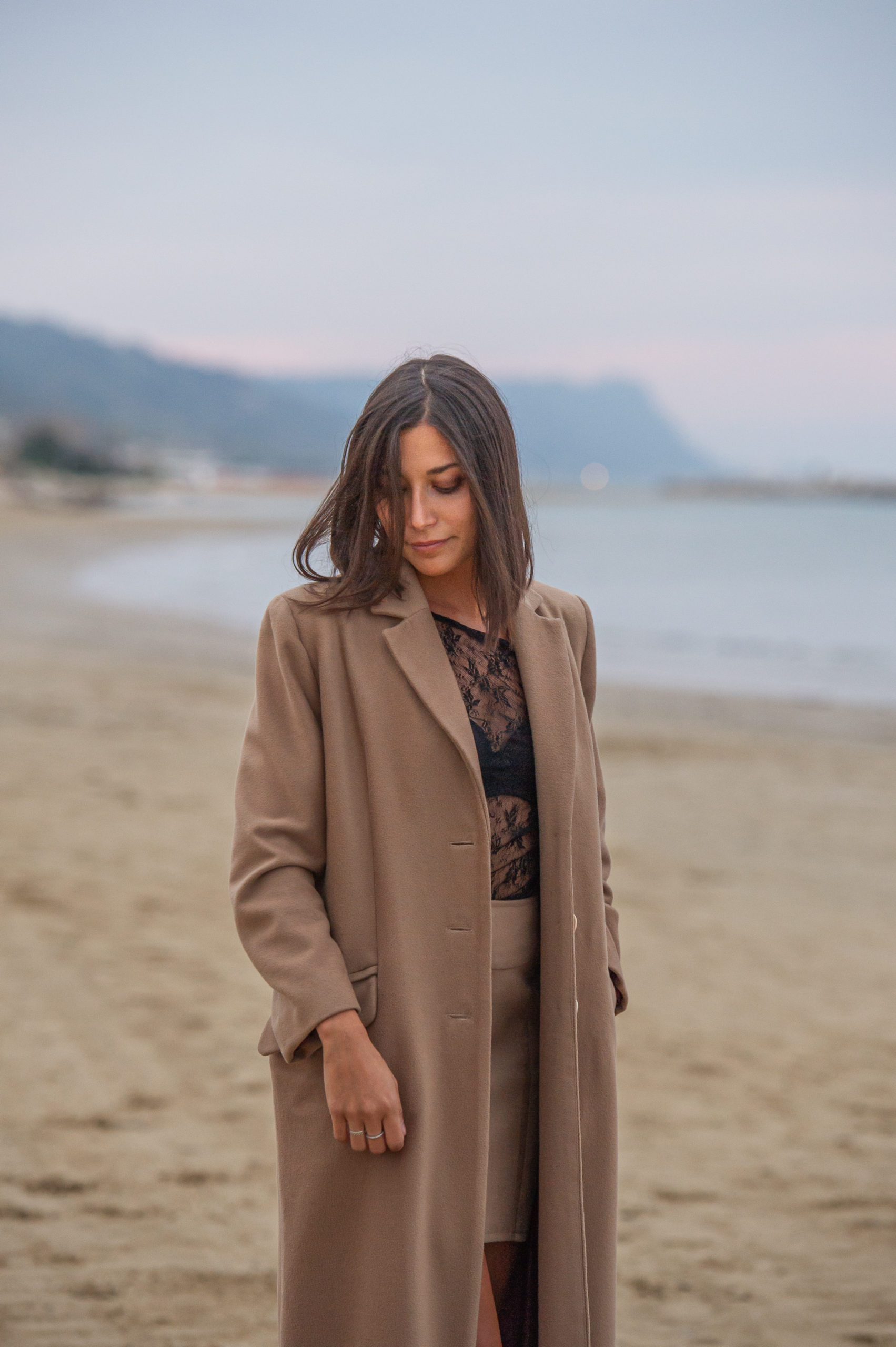 Chiara indossa un cappotto su misura in riva al mare